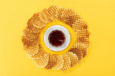 Photo pour Vue supérieure des gaufres en cercle avec la tasse de thé au milieu sur le jaune - image libre de droit