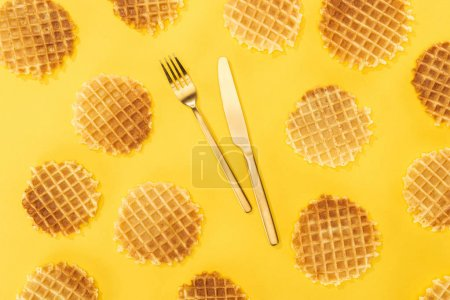 Photo for Top view of waffles with cutlery in middle isolated on yellow - Royalty Free Image