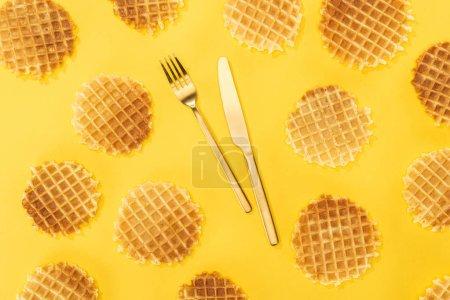 Photo pour Vue de dessus des gaufres avec couverts au milieu isolé sur jaune - image libre de droit