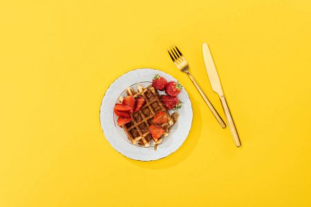 Photo for Top view of plate with tasty waffle and strawberries for breakfast on yellow - Royalty Free Image