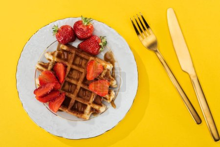 Photo for Top view of plate with tasty waffle for breakfast on yellow - Royalty Free Image