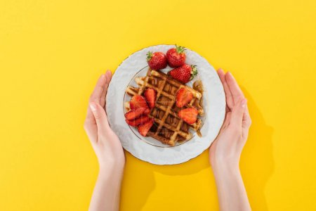Photo for Cropped view of woman holding plate with waffle and strawberries on yellow - Royalty Free Image