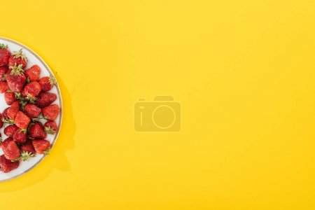 Photo for Top view of plate with strawberries on yellow - Royalty Free Image