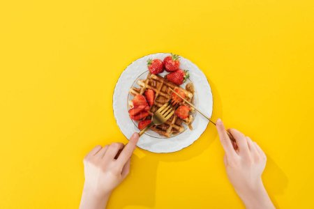 Photo for Cropped view of woman cutting waffle on plate on yellow - Royalty Free Image