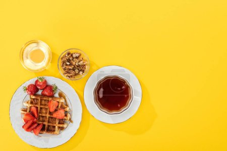 Photo for Top view of waffles, berries, honey and nuts on yellow - Royalty Free Image