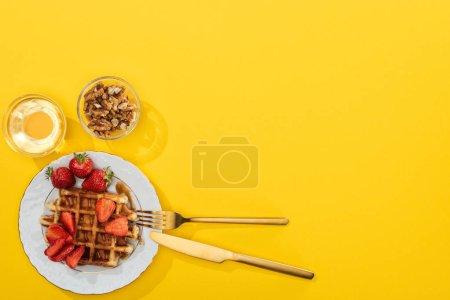 Foto de Vista superior de gofres, bayas, miel y frutos secos cerca de cubiertos en amarillo - Imagen libre de derechos