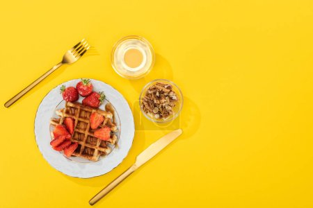 Photo for Top view of served breakfast with waffles, berries, honey and nuts near cutlery on yellow - Royalty Free Image
