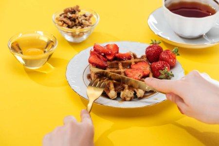 Photo pour Vue recadrée de gaufres de coupe de femme sur l'assiette près du bol et de la tasse avec le thé sur le fond jaune - image libre de droit