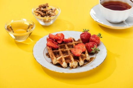 Photo for Served breakfast with waffle and strawberries on plated, honey, nuts and tea on yellow background - Royalty Free Image