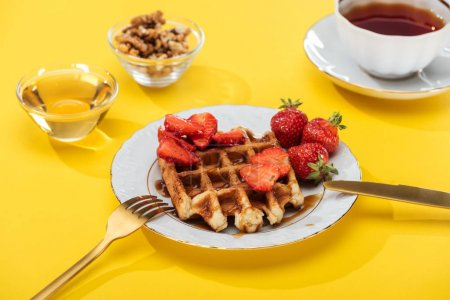 Photo for Served breakfast with waffle and strawberries on plated near cutlery, honey, nuts and tea on yellow background - Royalty Free Image