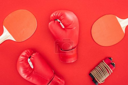 Photo for Top view of boxing gloves near ping pong rackets near skipping rope isolated on red - Royalty Free Image