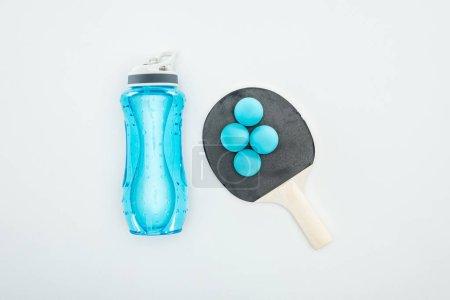 Photo pour Vue du dessus de la bouteille de sport bleue près des balles de ping-pong et des raquettes isolées sur blanc - image libre de droit
