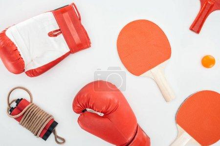 Photo pour Vue de dessus des gants de boxe près des raquettes de ping pong rouge et corde à sauter isolée sur blanc - image libre de droit