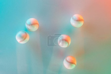 Photo for Top view of white and leather softballs on pink and blue - Royalty Free Image