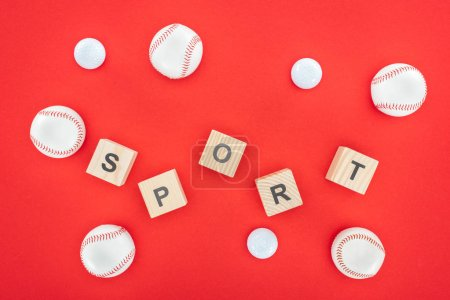 sport letters on wooden cubes near softballs isolated on red