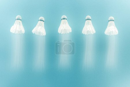 Photo for Motion blur of white shuttlecocks with feathers flying on blue - Royalty Free Image