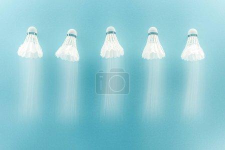 Foto de Desenfoque de movimiento de pollas blancas con plumas volando sobre azul - Imagen libre de derechos