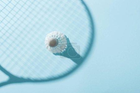 Photo pour Vue supérieure de volant blanc avec des plumes près de l'ombre de la raquette de badminton sur le bleu - image libre de droit