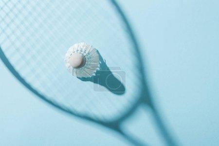 Photo pour Vue supérieure de volant avec des plumes blanches près de l'ombre de la raquette de badminton sur le bleu - image libre de droit