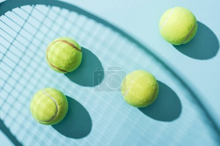 Photo for Top view of tennis balls near shadow of tennis racket on blue - Royalty Free Image