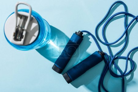 Photo for Top view of sport bottle with water near jumping rope on blue - Royalty Free Image