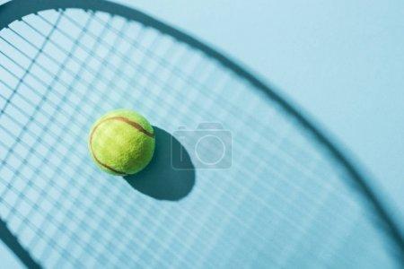 Photo pour Vue supérieure de la bille de tennis près de l'ombre de la raquette de tennis sur le bleu - image libre de droit