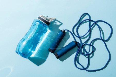 Photo pour Vue du dessus de la bouteille de sport avec de l'eau près de corde à sauter sur bleu - image libre de droit