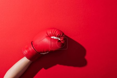 Photo for Cropped view of woman in boxing glove on red - Royalty Free Image