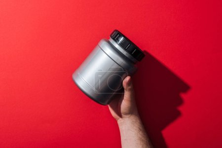 Photo for Cropped view of man holding grey jar on red - Royalty Free Image