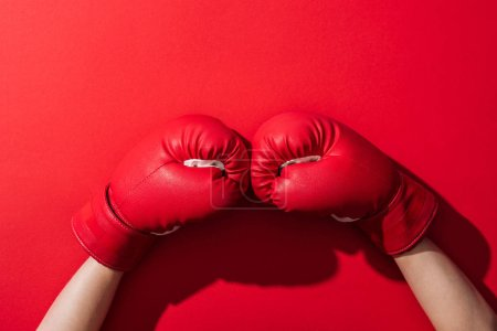 Photo for Cropped view of woman in pair of boxing gloves on red - Royalty Free Image