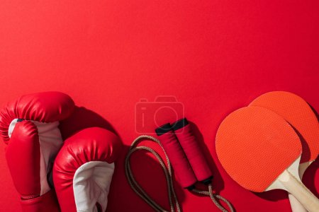 Photo for Top view of boxing gloves near red ping pong rackets and skipping rope on red - Royalty Free Image