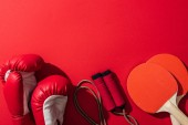 """Постер, картина, фотообои """"top view of boxing gloves near red ping pong rackets and skipping rope on red """""""
