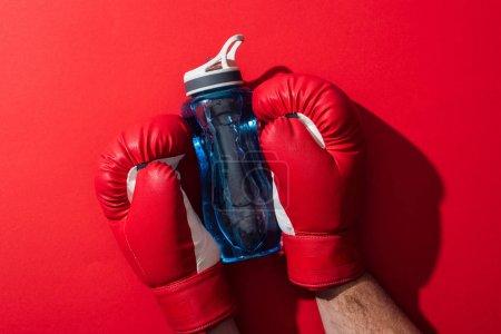 Photo pour Vue recadrée de la bouteille de sport de fixation de boxeur avec des gants de boxe sur le rouge - image libre de droit
