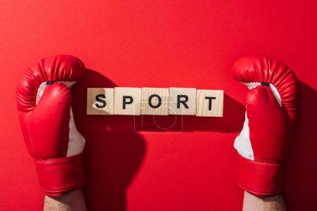 Photo pour Vue recadrée de l'homme dans des gants de boxe près des cubes en bois avec le lettrage de sport sur le rouge - image libre de droit