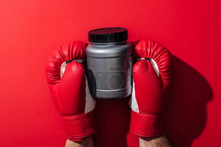 Foto de Vista recortada del hombre sosteniendo tarro gris en guantes de boxeo en rojo - Imagen libre de derechos