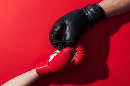 Photo for Cropped view of man and woman in boxing gloves on red - Royalty Free Image
