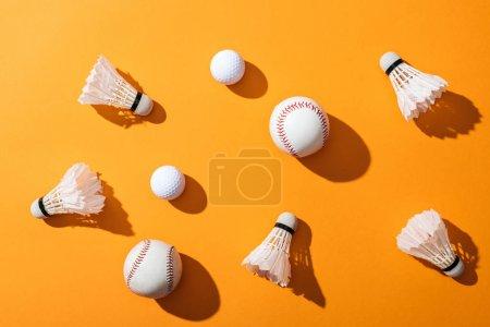 Photo pour Vue supérieure des volants avec des plumes près des softballs et des boules de golf sur le jaune - image libre de droit