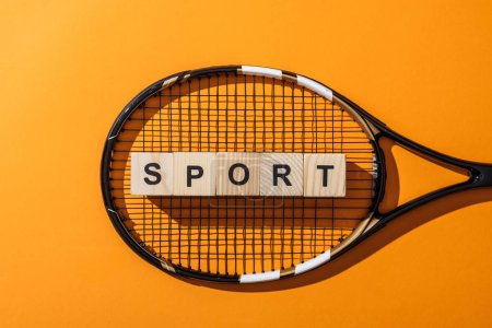 Photo for Top view of wooden cubes with sport lettering near tennis racket on yellow - Royalty Free Image