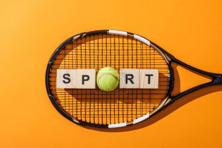 Photo for Top view of wooden cubes with sport lettering near tennis ball and tennis racket on yellow - Royalty Free Image