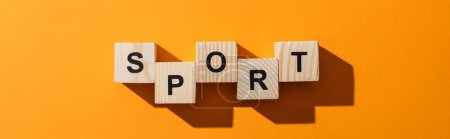 Photo for Panoramic shot of wooden blocks with sport lettering on yellow - Royalty Free Image