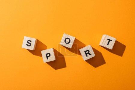 Photo pour Vue de dessus des cubes en bois avec des lettres de sport sur jaune - image libre de droit