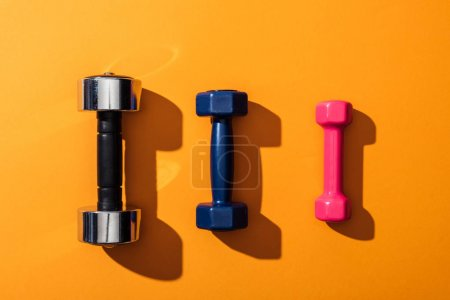 Photo for Top view of black, blue and pink metallic dumbbells on yellow - Royalty Free Image