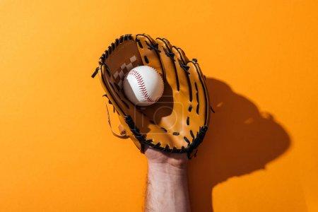 Photo pour Vue recadrée de l'homme retenant le softball dans le gant brun de base-ball sur le jaune - image libre de droit