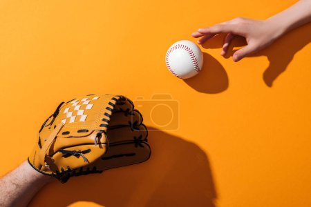 Photo pour Vue recadrée de l'homme dans le gant brun de base-ball près du softball et de la femme sur le jaune - image libre de droit