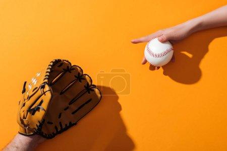 Photo pour Vue recadrée de l'homme dans le gant brun de base-ball près de la femme retenant le softball sur le jaune - image libre de droit