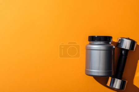 Photo for Grey jar with protein near heavy metallic dumbbell on yellow - Royalty Free Image
