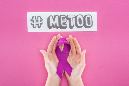 Photo pour Vue recadrée de la femme tenant un ruban de sensibilisation violet près du papier avec hashtag moi trop isolé sur rose - image libre de droit