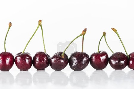 Photo for Red, fresh, whole cherries with water drops on white background with copy space - Royalty Free Image