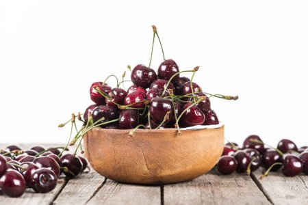 Photo for Red, fresh, whole and ripe cherries covered with droplets on bowl on wooden table - Royalty Free Image
