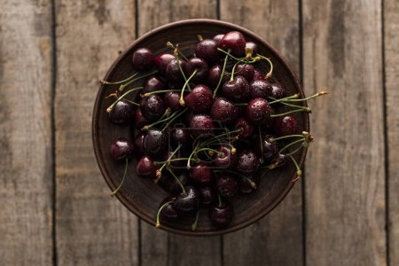 Photo for Top view of red, fresh, whole and ripe cherries covered with droplets on plate on wooden surface - Royalty Free Image